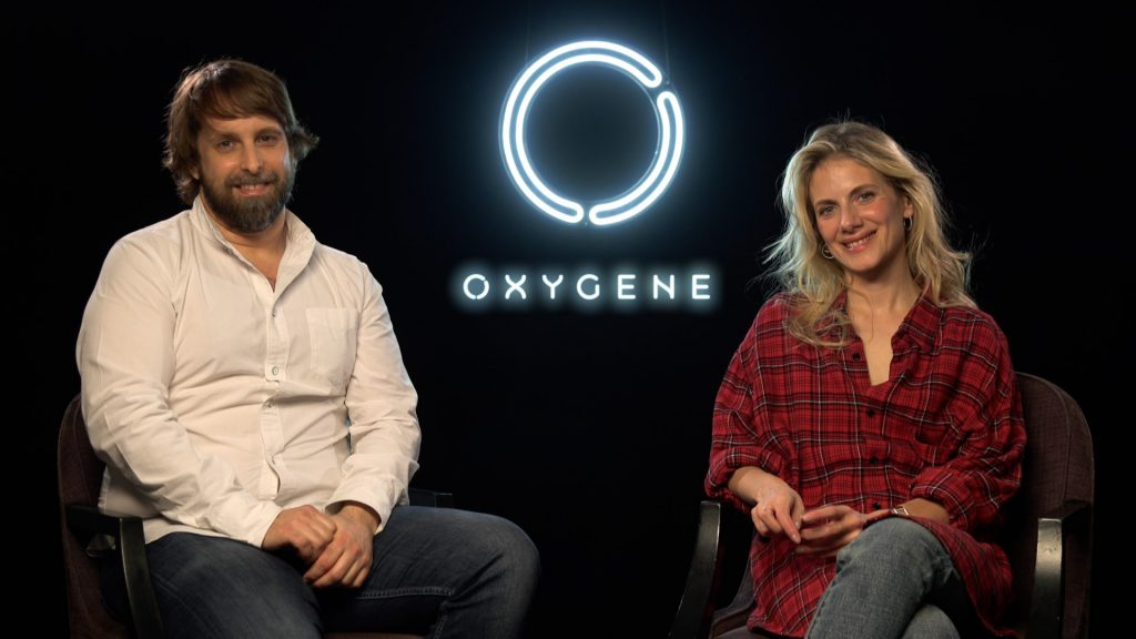 """Alexandre Aja and Mélanie Laurent sitting in front of a black background with a neon sign of the """"Oxygen"""" title treatment between them"""