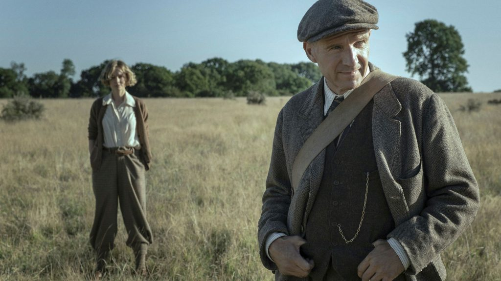 Ralph Fiennes's character from The Dig standing in a feild wearing a tweed suit as Carey Mulligan's character stands behind him, hands in pockets
