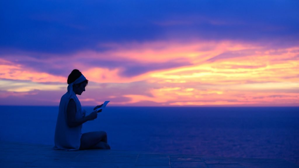 Shailene Woodley's character from The Last Letter From Your Lover reading a letter, sitting overlooking a calm sea at sunset
